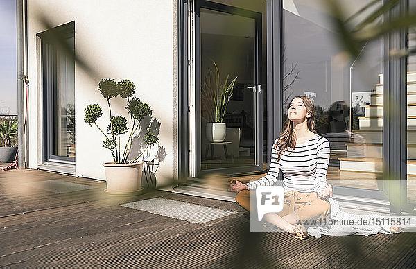 Junge Frau  die zu Hause auf der Terrasse sitzt und Yoga praktiziert