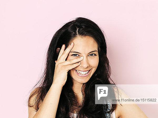 Porträt einer jungen lächelnden Frau mit schwarzen Haaren und Hand im Gesicht  vor rosa Hintergrund