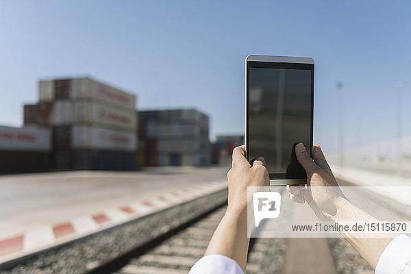Nahaufnahme von Händen  die eine Tablette auf der Eisenbahn in der Nähe von Frachtcontainern auf einem Industriegelände halten