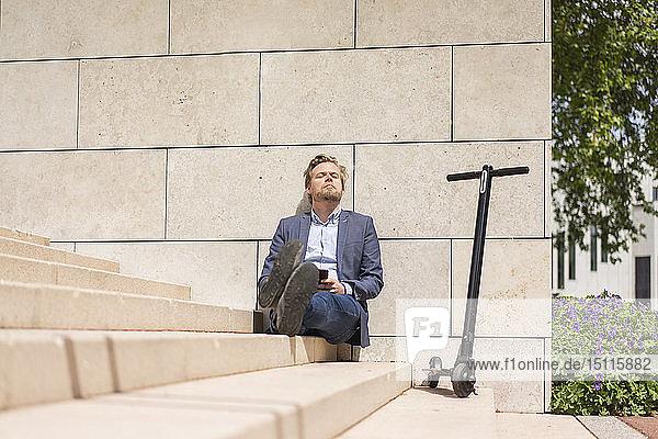 Geschäftsmann mit E-Scooter und Smartphone sitzt entspannt auf Stufen