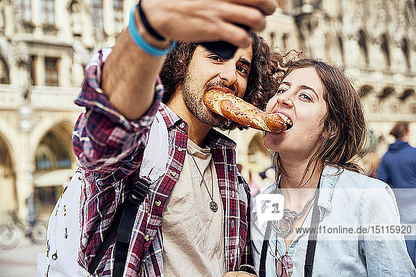 Young couple taking a selfie with brezel in the mouth  Munich  Germany