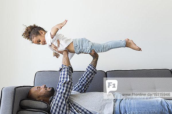 Glückliche Vater und Tochter spielen zu Hause auf der Couch