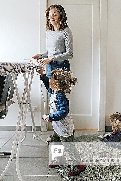 Mutter und Tochter zu Hause mit Bügelbrett