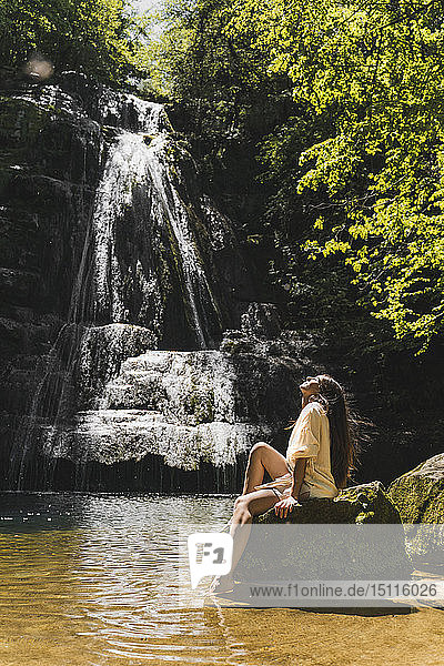 Young woman sitting on rock at a waterfall  Garrotxa  Spain
