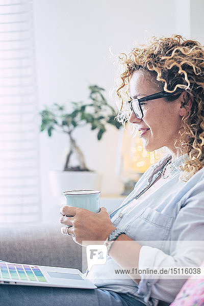Smiling woman with coffee mug using laptop on couch at home