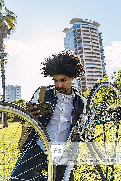 Gelegenheits-Geschäftsmann mit Handy und Fahrrad im Stadtpark  Barcelona  Spanien