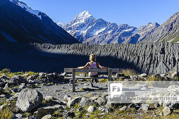 Woman stiitng on a bench and enjoying the view of Mount Cook  South Island  New Zealand