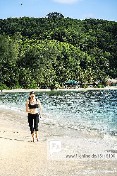 Seychellen  Mahe  Takamaka Beach  reife Frau joggt am Strand