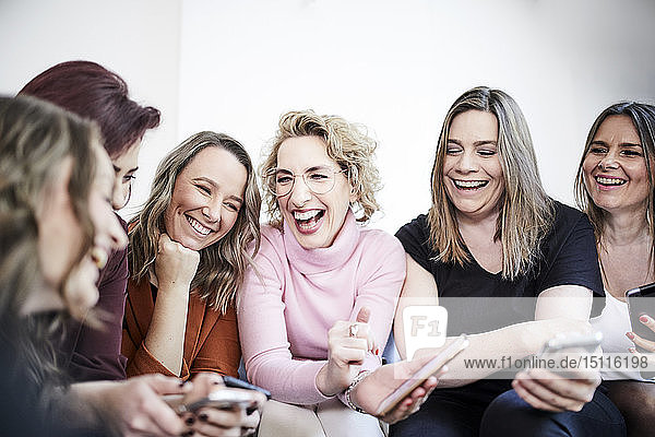 Group of six laughing women with smartphones