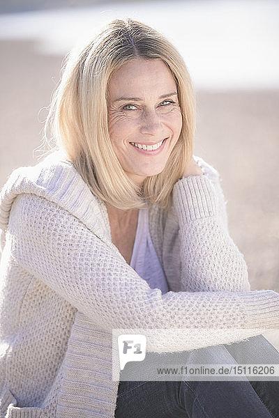 Porträt einer lächelnden reifen Frau  die im Freien sitzt