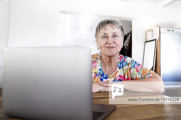 Portrait of smiling senior woman sitting at table at home using laptop