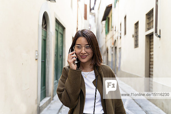 Italy  Florence  young woman on cell phone in an alley