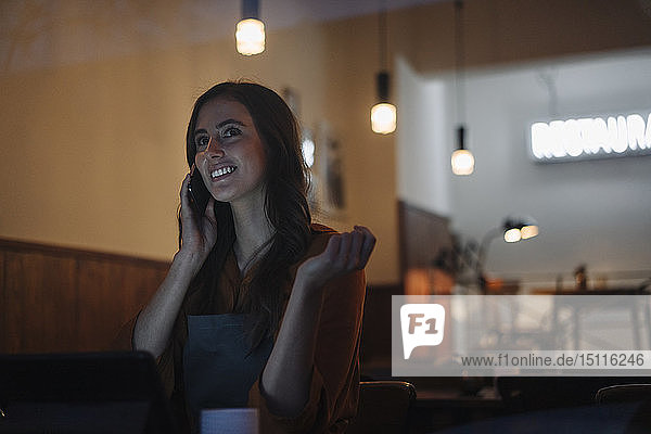 Young woman sitting at table in a restaurant with cell phone and tablet