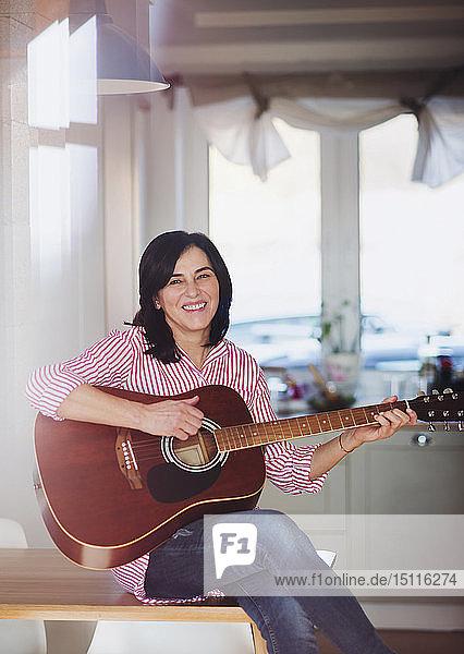 Porträt einer lächelnden reifen Frau  die zu Hause Gitarre spielt