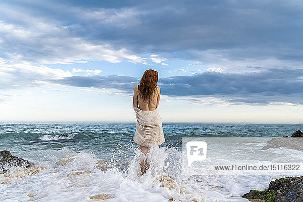 Rückenansicht einer rothaarigen  hemdlosen jungen Frau  die vor dem Meer steht