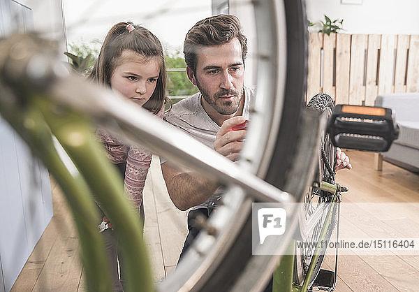 Junger Mann und kleines Mädchen reparieren gemeinsam Fahrrad