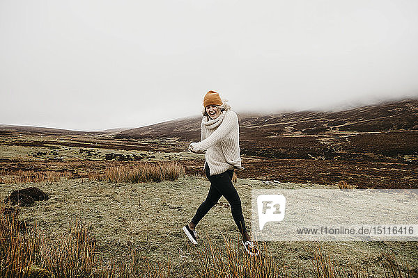 UK  Scotland  Isle of Skye  happy young woman running in rural landscape