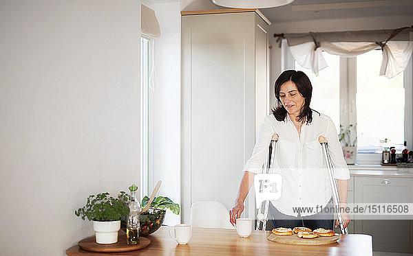 Reife Frau mit Krücken  allein zu Hause  Küchentisch decken