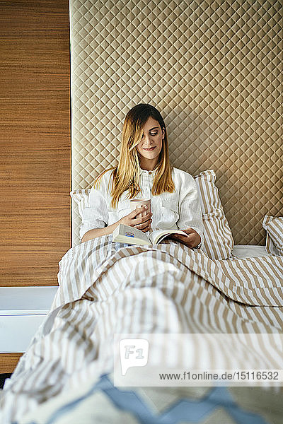Woman sitting in bed  reading a book