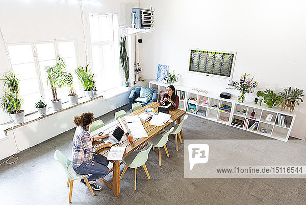 Two women working at table in modern office