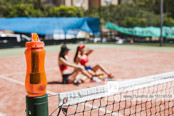 Orange drinking bottle with female tennis players sitting on court in background