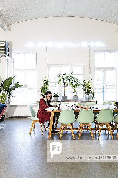 Woman working at table in modern office