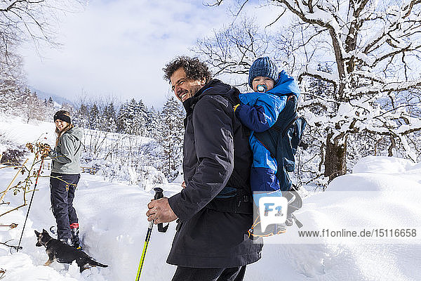 Father with son in the child carrier  mother and dog in Oberammergau in winter