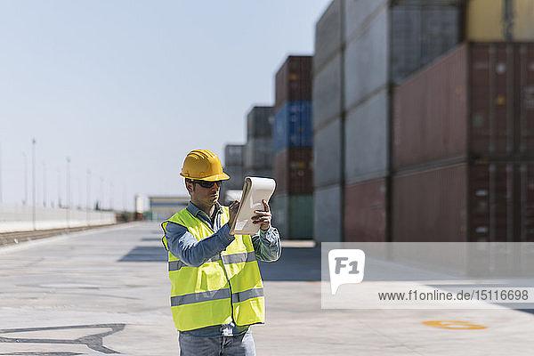 Arbeiter mit einem Notizblock in der Nähe von Frachtcontainern auf einem Industriegelände