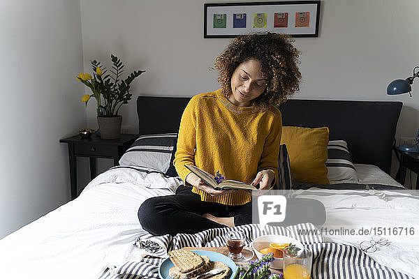 Frau sitzt im Bett  frühstückt gesund  liest Buch