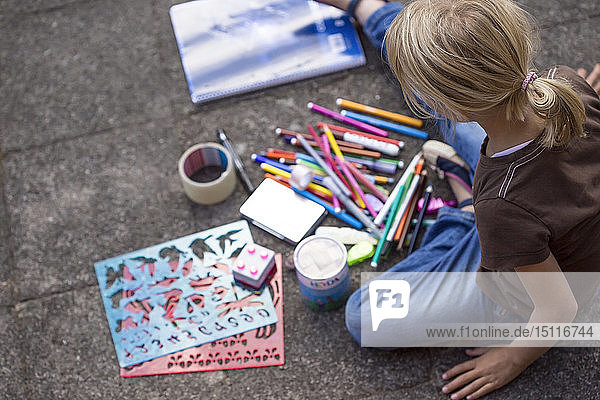 Girl sitting on pavement with many drawing materials