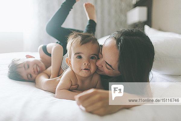 Mutter und zwei Jungen kuscheln zu Hause im Bett