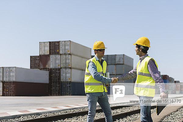Arbeiter schütteln Hände auf Eisenbahnschienen in der Nähe von Frachtcontainern auf einem Industriegelände