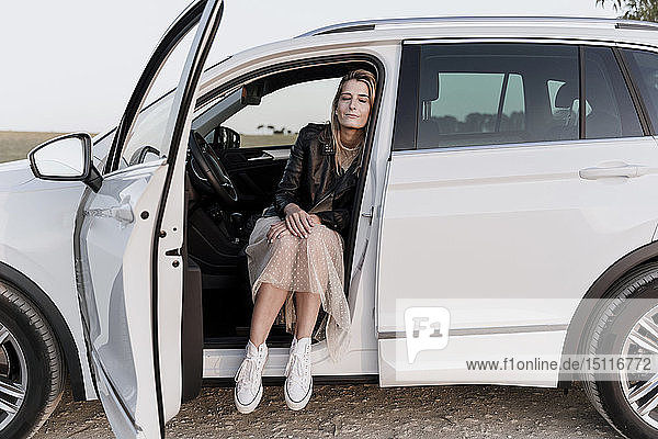 Blond woman with closed eyes  sitting in white car