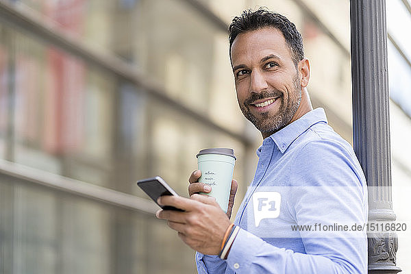 Smiling businessman with with takeaway coffee and cell phone in the city