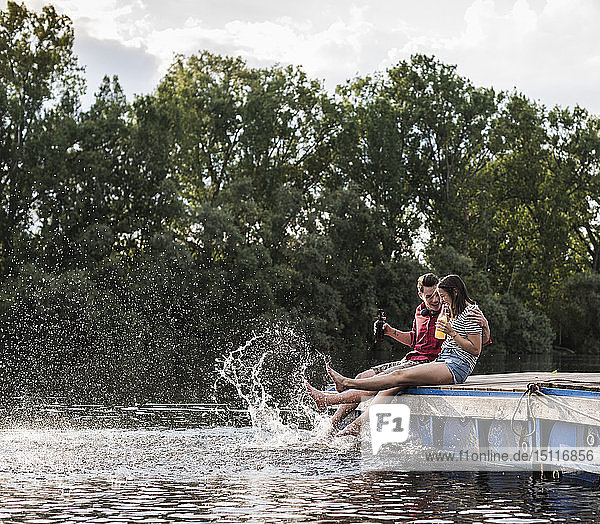 Young couple having a drink and splashing with water on jetty at a remote lake