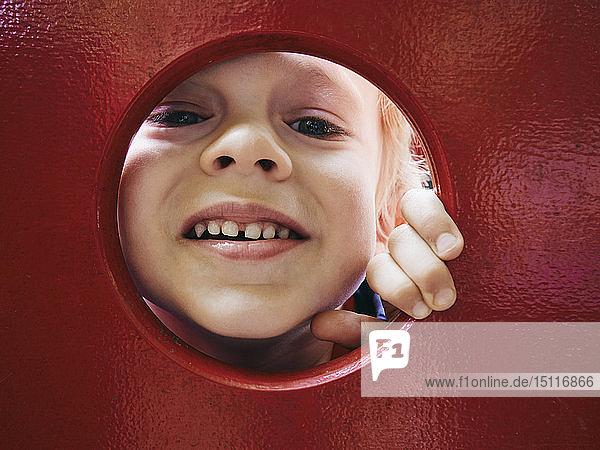 Porträt eines lächelnden kleinen Jungen  der durch ein Loch auf dem Spielplatz schaut