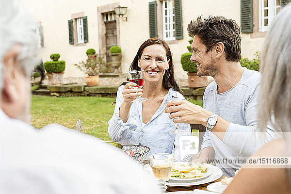 Happy family eating together in the garden  clinking glasses