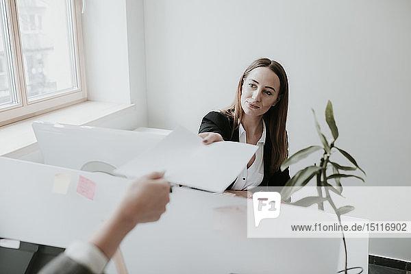 Zwei junge Frauen  die am Schreibtisch im Büro arbeiten und Papier aushändigen
