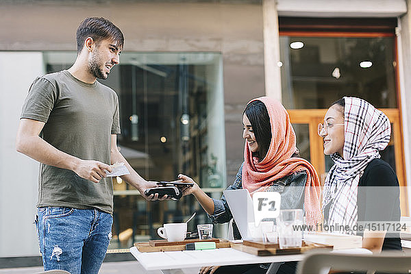 Young woman paying cashless with smartphone in a cafe
