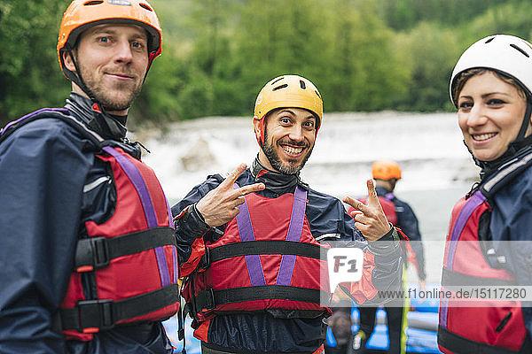 Glückliche Freunde bei einem Rafting-Kurs posieren am Flussufer
