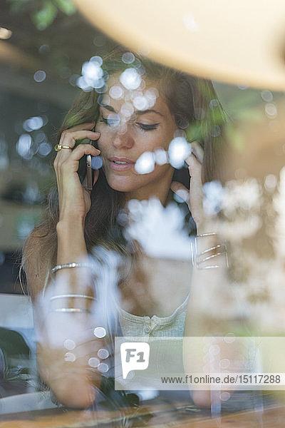 Junge Frau am Handy hinter der Fensterscheibe eines Cafés