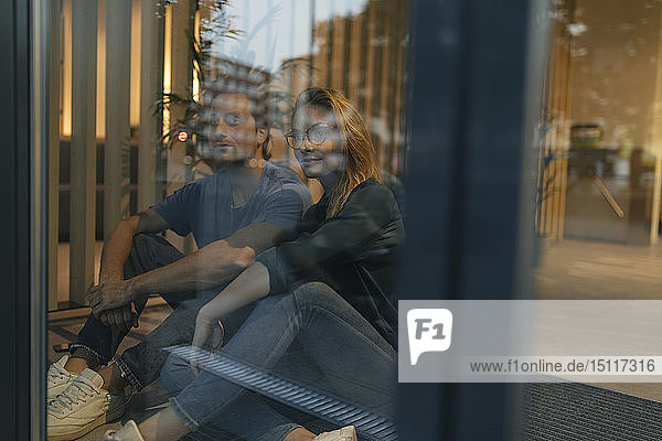Young man and woman sitting behind windowpane looking out