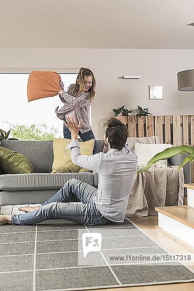 Junger Mann und kleines Mädchen bei einer Kissenschlacht im Wohnzimmer