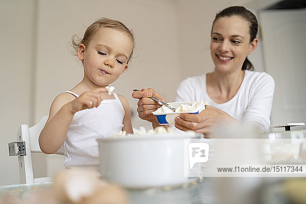 Mother and little daughter making a cake together in kitchen at home
