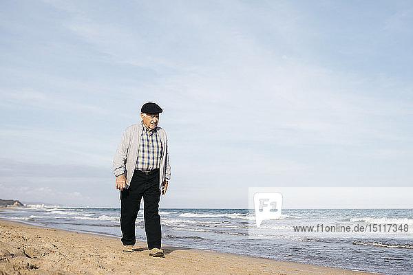 Älterer Mann beim Strandspaziergang im Frühling
