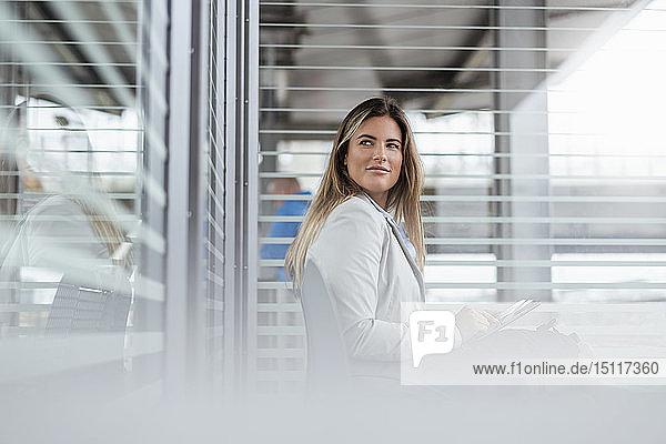 Junge Geschäftsfrau benutzt Tablette in einem Wartebereich