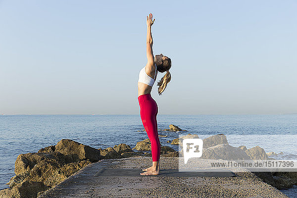 Young woman practicing yoga on the beach  doing sun salutations