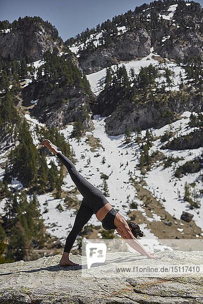 Junge Frau macht Yoga in der Natur,  nach unten gerichtete Hundehaltung