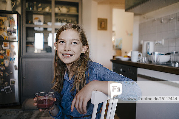 Happy girl sitting at kitchen table at home holding a glass