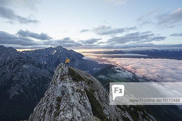 Austria  Tyrol  Gnadenwald  Hundskopf  male climber standing on rock in the morning light
